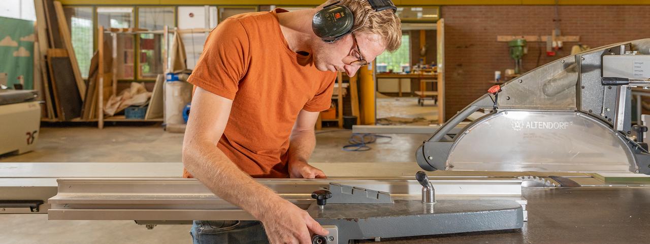 Jasper van der Hoeven zaagt houten planken voor een interieurproject.